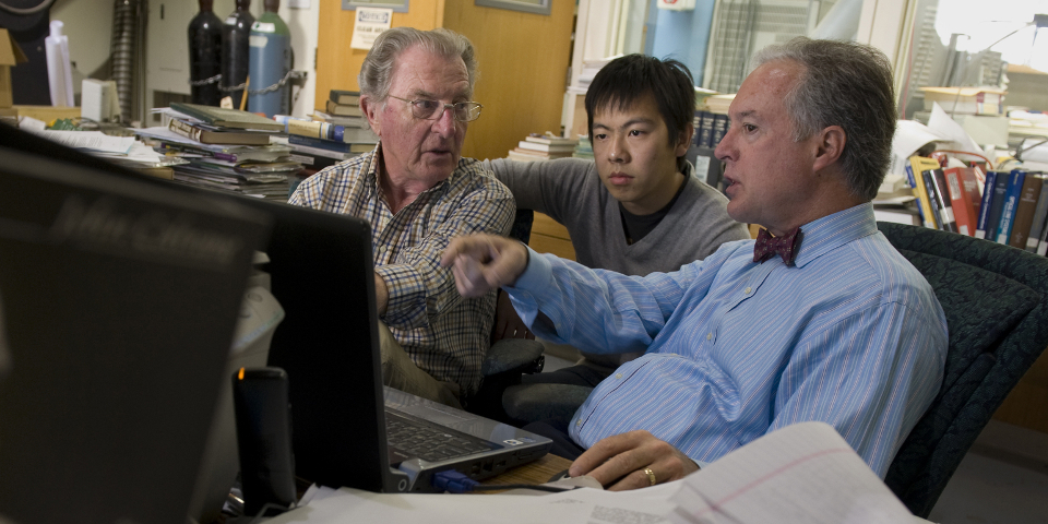 McWilliams (right) confers with research physicist Heinz Boehmer (left) and graduate student Shu Zhou in his lab in the basement of Reines Hall.